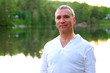Portrait of a proud healthy caucasian man, 50, wearing a white suit, after a meditation session by the river at the sunset.