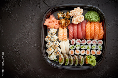 Poster Sushi bar Japanese food concept. Catering, various kinds of sushi on plate or platter set. Chopsticks, ginger, soy sauce, wasabi. Placed on stone black background in plastic delivery box.