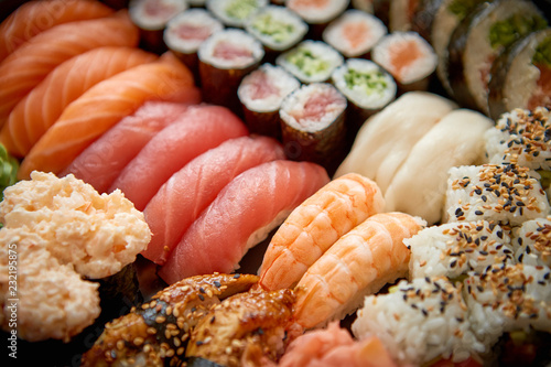 Close up of various types of japanese fresh prepared sushi. Served on a patter with ginger and wasabi.
