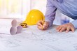 Architect working on construction blueprint. Architects