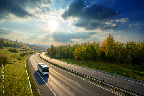 Fényképezés Three white buses traveling on the asphalt highway between deciduous forest in autumn colors under the radiant sun and dramatic clouds