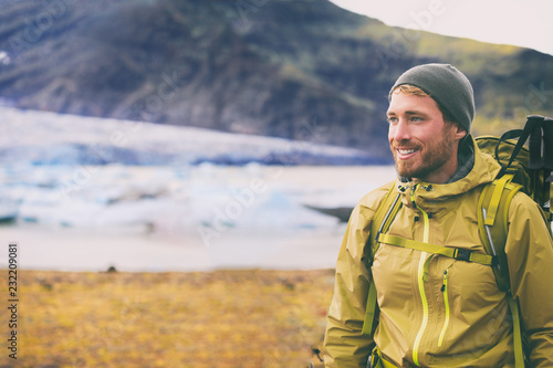 Fototapeta Winter hike on snow mountain happy hiker man walking in ice wilderness in Iceland . Europe travel adventure trek in nature landscape. Person wearing hat and jacket for cold weather, bag, hiking poles. obraz
