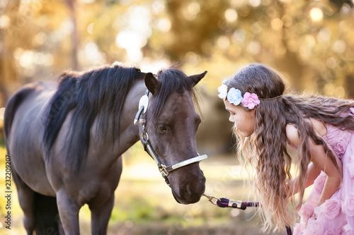 Fotografija Cute little girl and pony in a beautiful park