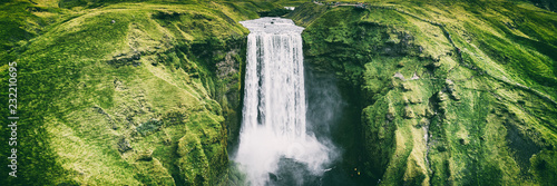 Cascades Iceland waterfall Skogafoss banner nature landscape. Panoramic destination in Icelandic famous world landmark tourist attraction on South Iceland. Aerial drone view of top waterfall.