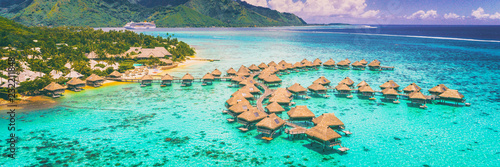 Travel vacation Tahiti hotel ocean beach paradise of overwater bungalows resort in coral reef lagoon ocean. View from above at sunset of Moorea, French Polynesia, Tahiti, South Pacific Ocean.
