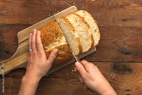 Fotografie, Obraz  Slicing through a loaf of bread.