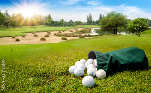 Golf Balls for training in green fabric bag on the golf course in morning. The concept of playing sport is to relax in vacation day