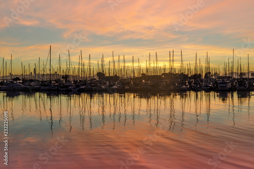 Colors of Emeryville Marina. Sailboats moored in San Francisco Bay with sunset skies and water reflections. Alameda County, California, USA.