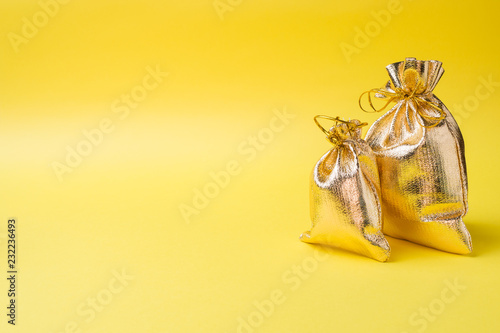 Fototapeta Christmas new year concept. Golden gift bag on a yellow background. Copy space obraz na płótnie