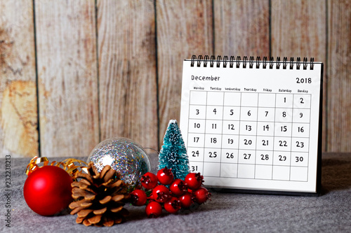 Obraz December 2018 calendar and Christmas decoration - baubles, cone and rowanberry on the soft table and wooden wall in the background - fototapety do salonu