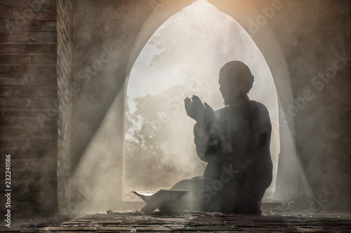 Fotografia Silhouette of muslim male praying in old mosque with lighting and smoke backgrou