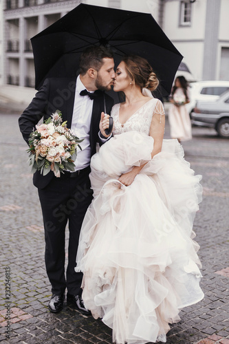 Leinwand Poster Gorgeous bride and stylish groom walking under umbrella in rainy street and kissing