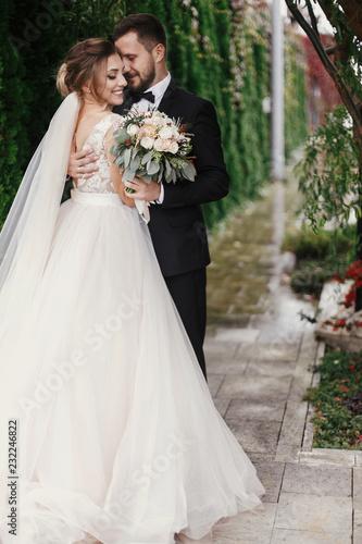 Obraz Gorgeous bride and stylish groom gently hugging on background of green trees. Sensual wedding couple embracing. Romantic moments of newlyweds. Modern wedding photo - fototapety do salonu