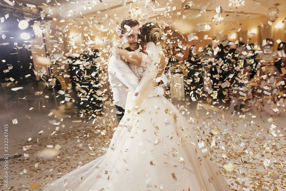 Fototapety, obrazy: Gorgeous bride and stylish groom dancing under golden confetti at wedding reception. Happy wedding couple performing first dance in restaurant. Romantic moments