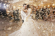canvas print picture - Gorgeous bride and stylish groom dancing under golden confetti at wedding reception. Happy wedding couple performing first dance in restaurant. Romantic moments