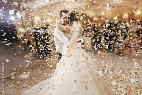 Gorgeous bride and stylish groom dancing under golden confetti at wedding reception Fotobehang