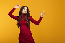 Attractive Bright Young Woman In Red Dress Is Posing On Orange Background.