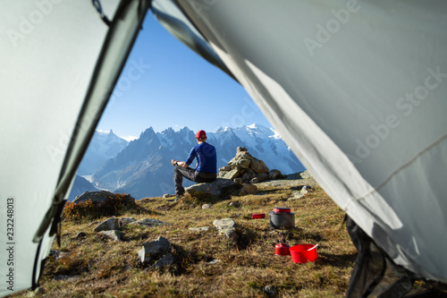 Hiker enjoying the view and a cup of coffe at his campsite in the mountains Wallpaper Mural