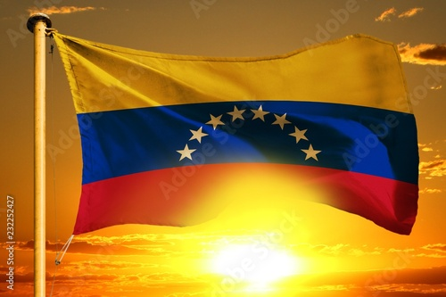 Fotografía  Venezuela flag weaving on the beautiful orange sunset with clouds background