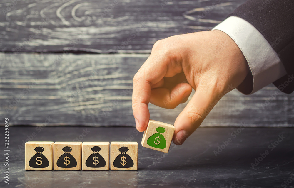 Fototapeta Businessman puts a block with a picture of dollars. The capital accumulation and successful business. Increased budget and profits in the team. Increase investment fund. Saving money. Economic boom