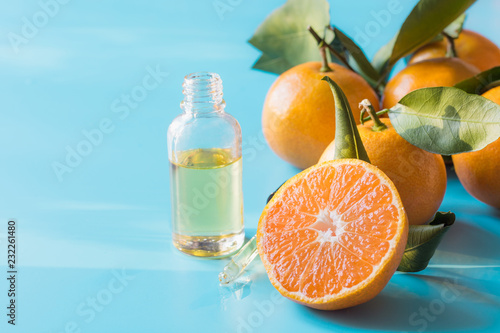 Essential oil of orange mandarin in glass bottle over pastel blue background. Skincare concept.