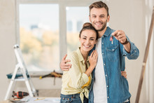 Happy Young Couple Holding Key From New Apartment And Smiling At Camera