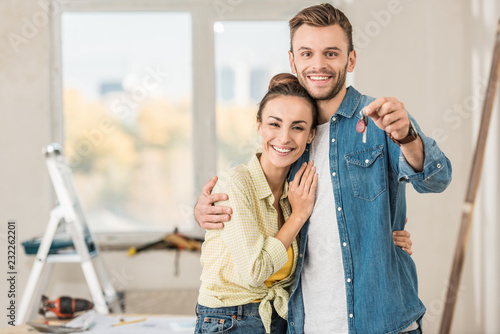 Fototapeta  happy young couple holding key from new apartment and smiling at camera