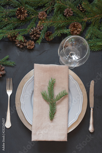 Tuinposter Restaurant Christmas table setting with silverware and dark evergreen decor. Top view. Holiday Centerpieces.