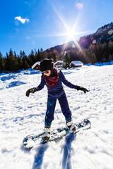Fototapeta Girl learning snowboard