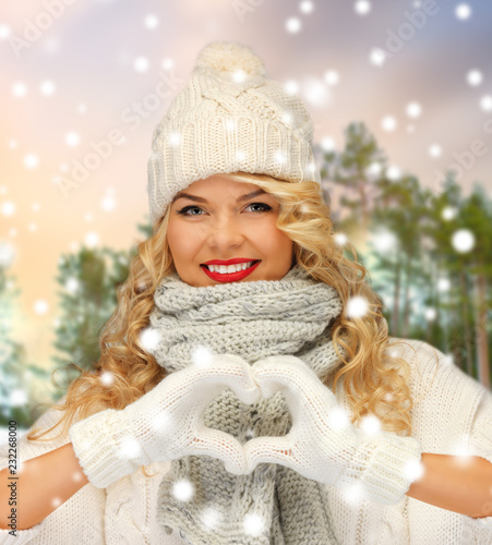 Foto op Plexiglas Hoogte schaal people, season and leisure concept - happy woman in hat, scarf and mittens showing hand heart over winter forest background