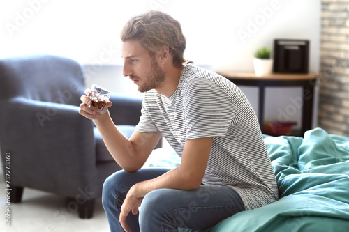 Poster de jardin Bar Depressed young man drinking alcohol at home