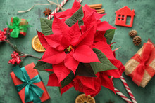 Christmas Flower Poinsettia With Gift Boxes And Decorations On Color Table