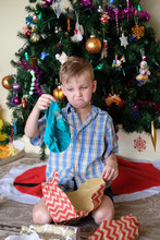 Young Boy Pulling A Funny Face Looking At An Unwanted Christmas Present