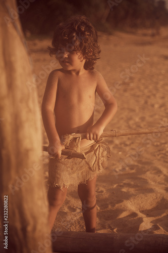 Photo  Mowgli boy with curly hair playing with bamboo stick