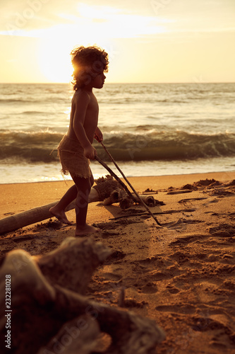 Photo  Mowgli boy with curly hair playing with sticks near ocean