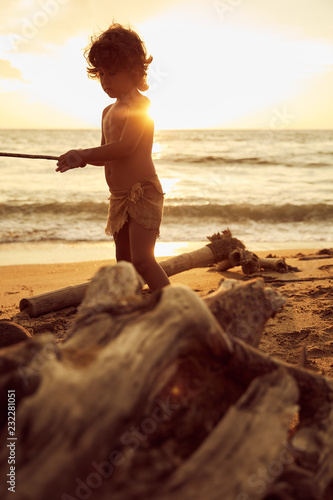 Photo  Mowgli boy with curly hair playing with stick near ocean