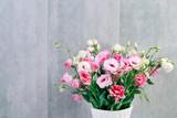 Pink eustoma (lisianthus) flowers on grey stone background.