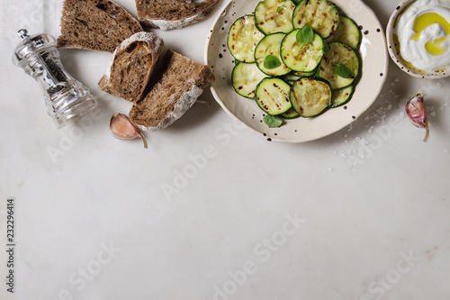 Grilled zucchini salad with yogurt dip and rye sliced bread in spotted ceramic plates over white marble background. Vegetarian food. Flat lay, space