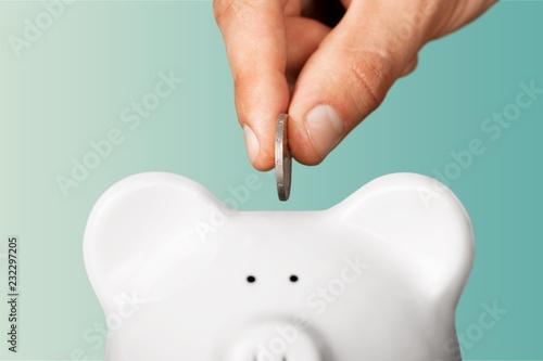 Fototapeta Hand putting coin to piggy bank obraz