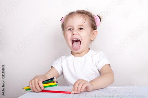 Fotografía  The girl draws in colored pencils
