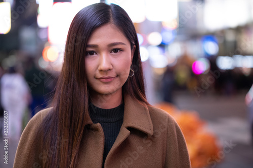 Photo Young Asian woman in city at night serious face