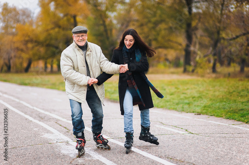 Happy pension. Active sport old people. The old man goes on rollers with his young daughter in the autumn park. Comic dance, a parody of the Swan Lake.