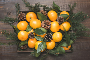 Fresh mandarins with leaves in box on wooden table. Christmas composition. Holiday Centerpieces.