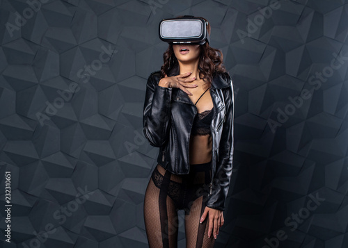 Beautiful girl is experiencing emotions with glasses of virtual reality.