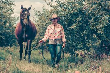 Fototapeta Western woman walking on green meadow with horse