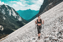 Young Woman Hiking On Steep Mountain Slope