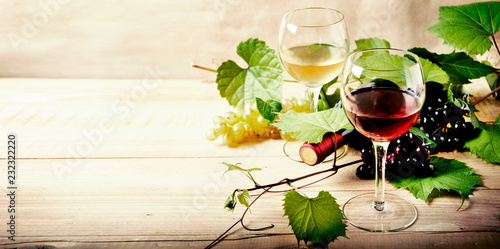 Fotografie, Obraz  Glass of red and white wine, bottle and grape vine on vintage wooden table