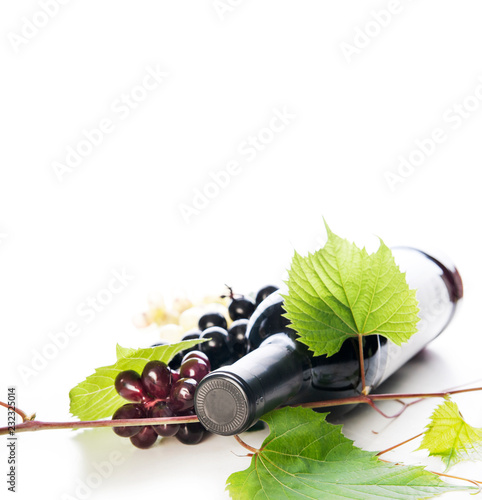 Obraz na plátně  Bottle of luxury red wine and grape vine isolated over white background