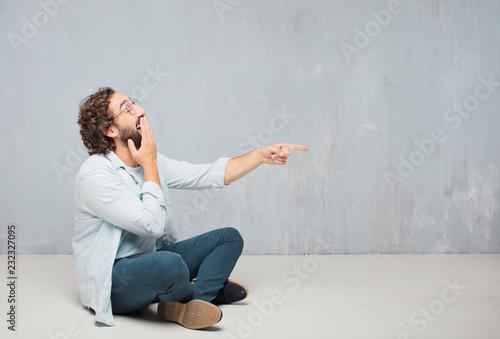 Valokuvatapetti young cool bearded man sitting on the floor