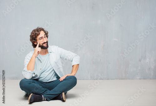 Fotomural  young cool bearded man sitting on the floor